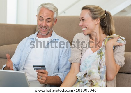 Happy couple shopping online on the couch at home in the living room - stock photo