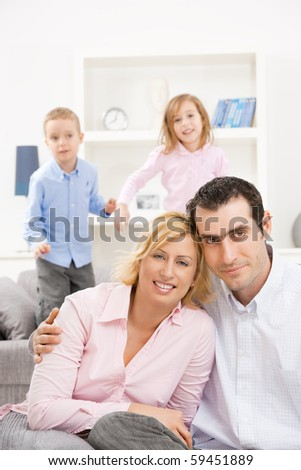 Happy couple sitting at floor at home, embracing. Their children jumping on couch in background.