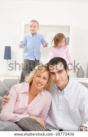 Happy couple sitting at floor at home, embracing. Two children jumping on couch in background.