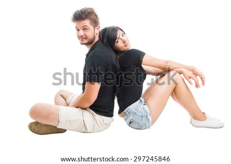 Happy couple sitting back to back or behind each other on white studio background - stock photo