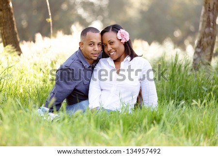 Happy couple sitting close together in a grassy park setting - stock photo