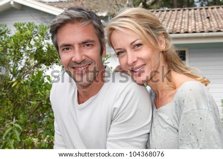 Happy couple sitting in from of their new home - stock photo