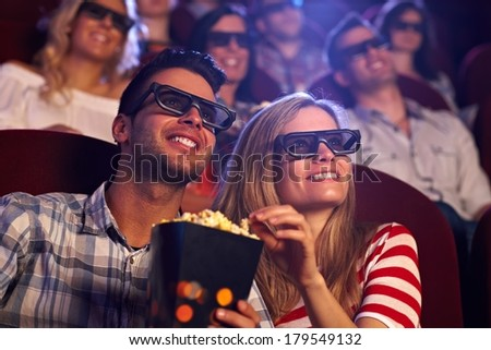 Happy couple sitting in movie theater, watching 3D movie, eating popcorn, smiling. - stock photo