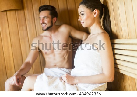 Happy couple sitting in sauna leaning to each other - stock photo