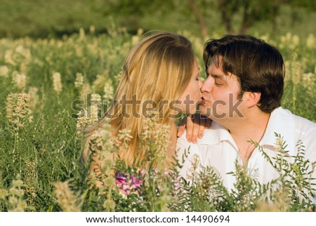 Happy couple sitting in the grass enjoying being together