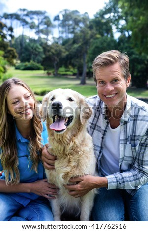 Happy couple sitting in the park with their dog - stock photo