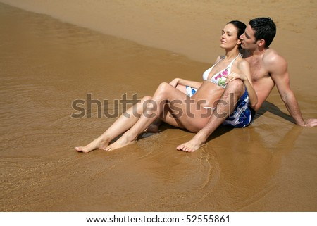 Happy couple sitting in the sand - stock photo