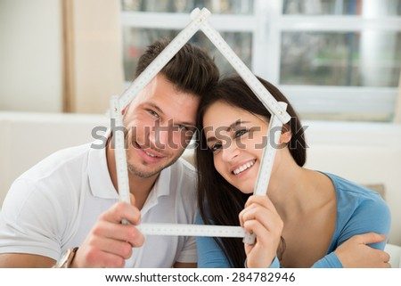 Happy Couple Sitting On Chair Holding Model House Made Up Of Measurement Tape - stock photo