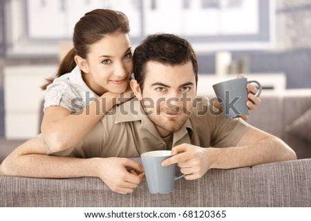 Happy couple sitting on sofa at home, drinking tea, smiling.
