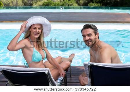 Happy couple sitting on sun lounger near pool - stock photo