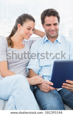 Happy couple sitting on the couch using tablet pc at home in the living room