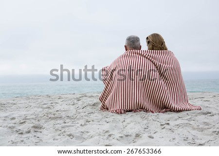 Happy couple sitting on the sand with blanket around them at the beach - stock photo