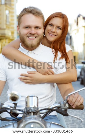 Happy couple sitting on the scooter. Portrait of a handsome bearded young man holding a handlebar and his beautiful red-haired girlfriend hugging him from the back smiling - stock photo