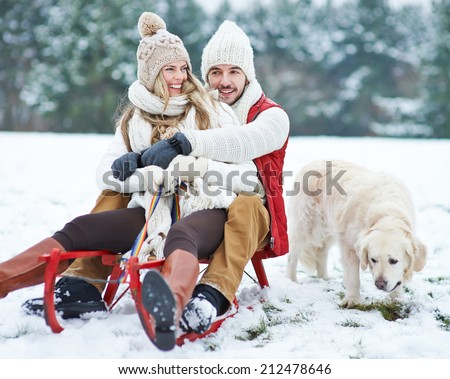 Happy couple sledding with toboggan and dog in winter - stock photo