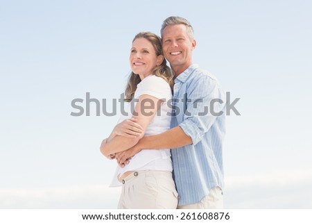 Happy couple smiling at camera at the beach - stock photo