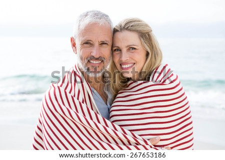 Happy couple smiling at camera with blanket around them at the beach - stock photo