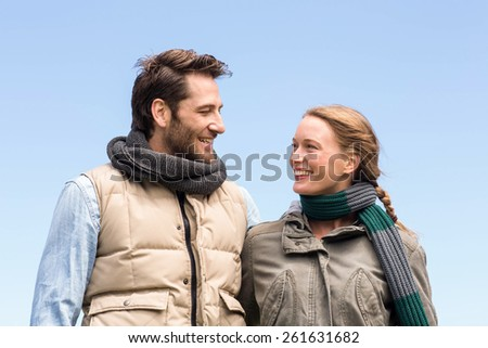 Happy couple smiling at each other in the countryside - stock photo