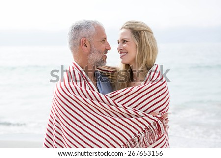 Happy couple smiling at each other with blanket around them at the beach - stock photo