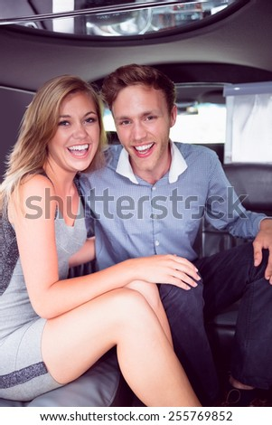 Happy couple smiling in limousine on a night out - stock photo