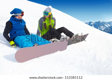 Happy  couple snowboarders in a ski resort - stock photo