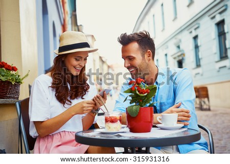 Happy couple spending time in outdoors cafe - stock photo