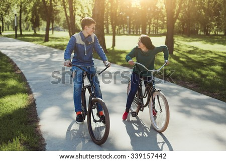 Happy couple spending time outdoors biking.Young couple riding on bicycles and laughs