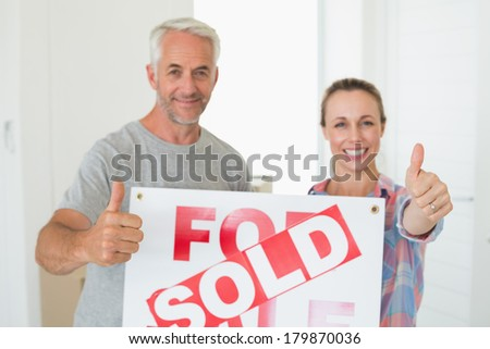 Happy couple standing and holding sold sign giving thumbs up in their new home
