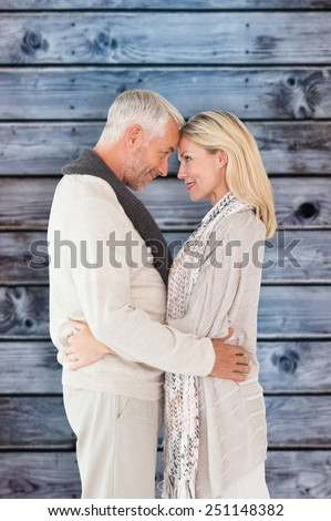 Happy couple standing and hugging against wooden background in blue - stock photo