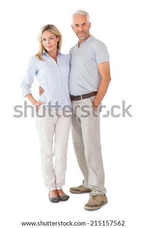 Happy couple standing and smiling at camera on white background - stock photo