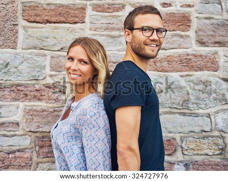 Happy Couple Standing Back to Back and Smiling at the Camera Against Brick Wall Background - stock photo