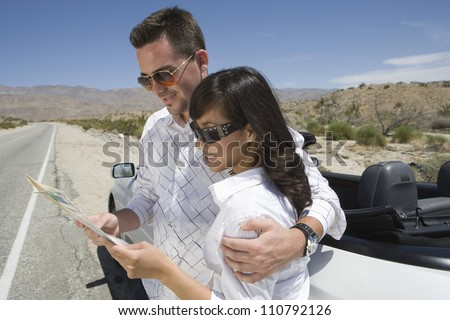 Happy couple standing by car looking at map on street - stock photo