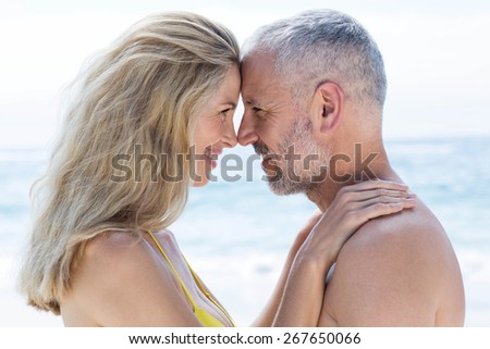 Happy couple standing by the sea and smiling at each other at the beach - stock photo