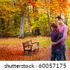 Happy couple standing embraced in the autumnal park looking to a bench - stock photo