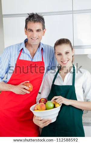 Happy couple standing in kitchen with bowl of fruit