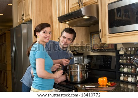 Happy couple standing in the kitchen together by the stove and smiling at the camera. Horizontally framed shot. - stock photo