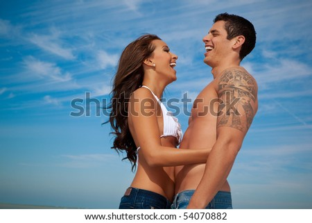 Happy couple standing, laughing - stock photo