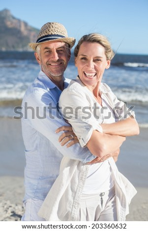 Happy couple standing on the beach together on a sunny day - stock photo
