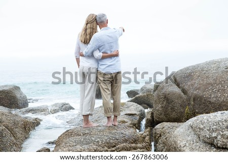 Happy couple standing on the rock and looking at the sea at the beach - stock photo