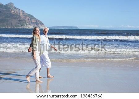 Happy couple strolling barefoot on the beach on a sunny day