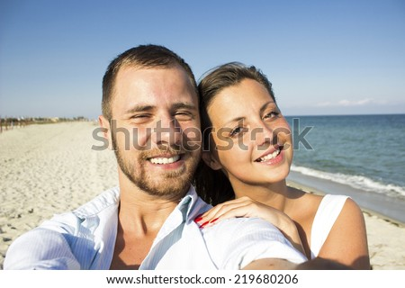 Happy couple taking a photo on a beach - stock photo