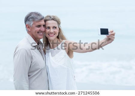 Happy couple taking a selfie at the beach - stock photo