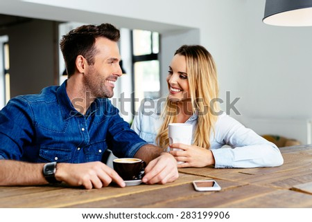 Happy couple talking at cafe looking at each other - stock photo