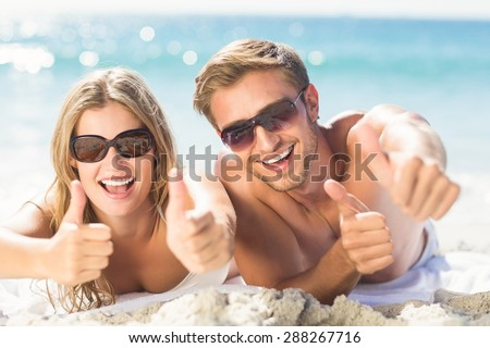 happy couple thumbs up at the beach - stock photo