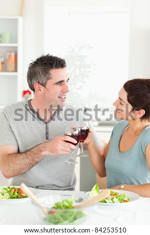 Happy couple toasting with redwine at the dinner table