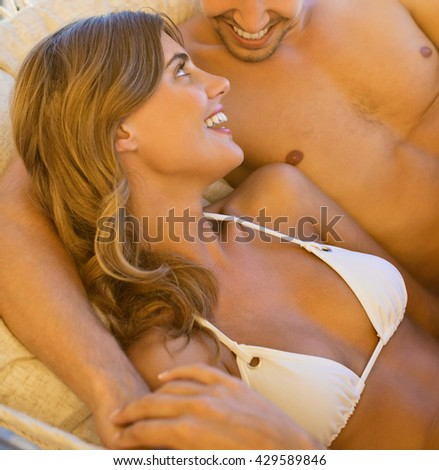 Happy couple together in the hammock at the beach - stock photo