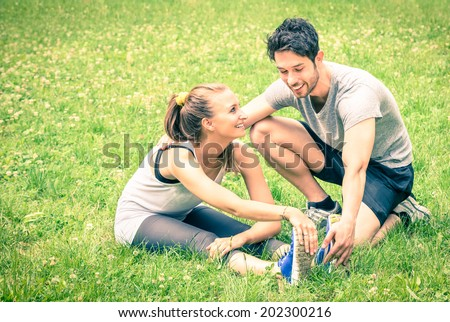 Happy couple training in the park - Young man and woman during summer workout and sport activity - Male and female fitness models stretching leg muscles after running - Vintage filtered look - stock photo