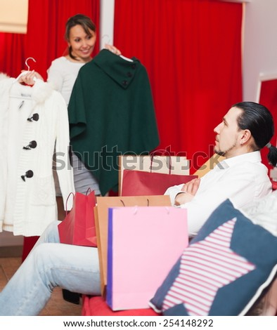 Happy couple trying coat in fitting-room at clothing store - stock photo