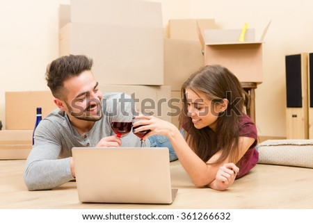 Happy couple using laptop computer in new home - stock photo
