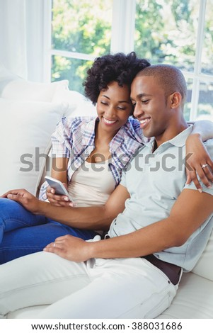 Happy couple using smartphone on the sofa in the living room