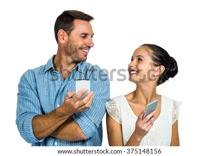 Happy couple using smartphones and looking at each other on white screen - stock photo